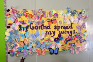 "A student-made poster at a school, with handmade butterflies and a painted quote from Lizzie's bully prevention campaign's theme song, ""Butterfly."" Photo by Lizzie Sider"