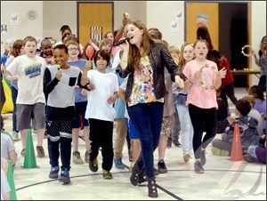 "Singer-songwriter and anti-bullying activist Lizzie Sider leads Camden Intermediate School students in a march around the school gym, Monday, as they sing Taylor Swift's song, ""Mean."" Sider opened her tour of North Carolina schools at Camden Intermediate School, Monday. Photo by Tom at Daily Advance"
